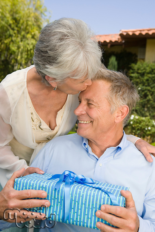 Senior woman giving husband birthday present and kissing him on forehead