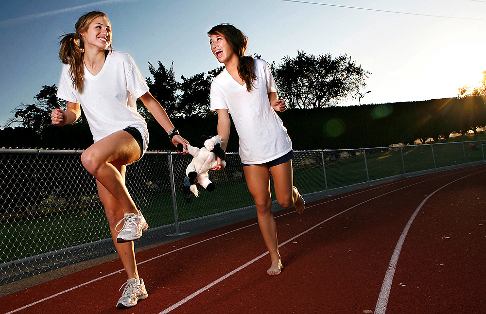 "Richland seniors Katie Mahoney, left, and Maggie Jones are leading the Bombers' cross country team and say training together on 10-mile runs is the most fun they have. They're seen here with ""The Cow,"" a good luck charm for the team that's passed down every year."