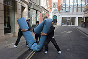 A team of Asian workmen manhandle a roll of industrial carpet in a side street and destined for a nearby shop in London's New Bond Street. Heaving the rolled rug into a manageable length, the men pick up the goods and carry it across the road and into nearby premises.