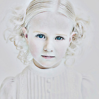 Young girl with blonde hair and blue eyes wearing white dress looking at camera