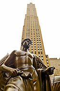 Manhattan, New York, U.S. - May 21, 2014 - At Rockefeller Plaza is bronze Mankind statue, Youth, by artist Paul Manship, with 30 Rockefeller Center looms behind, during a pleasant Spring Day, though skies are cloudy.