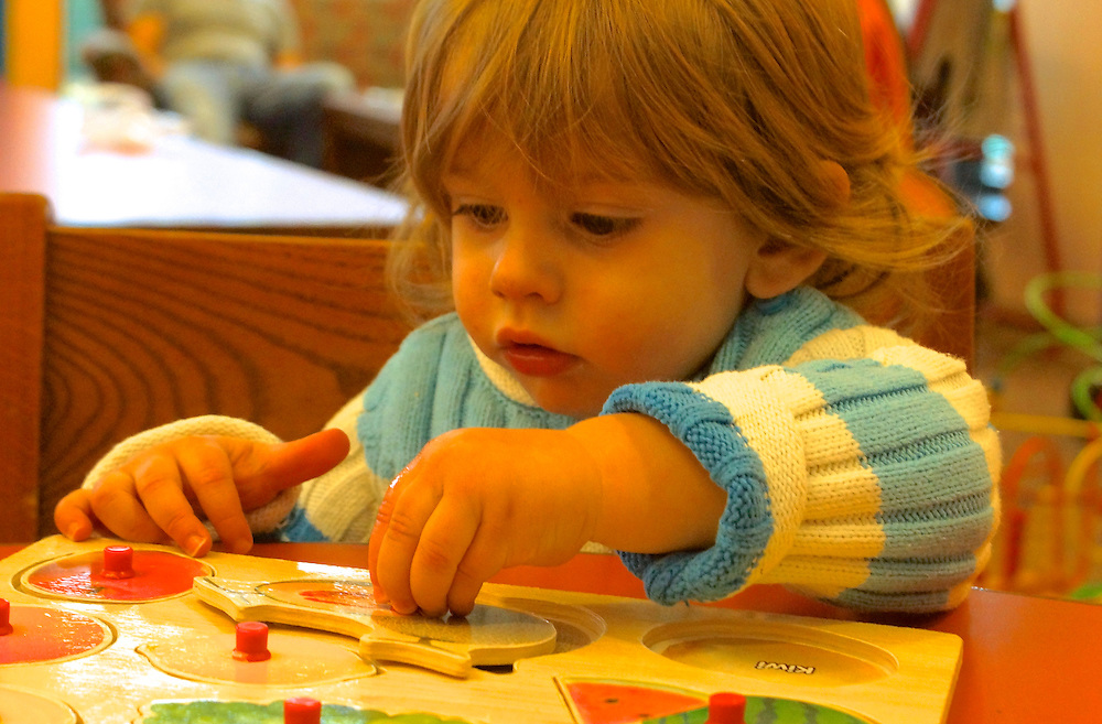 Child shows hand eye coordination with puzzle at age 15 months.
