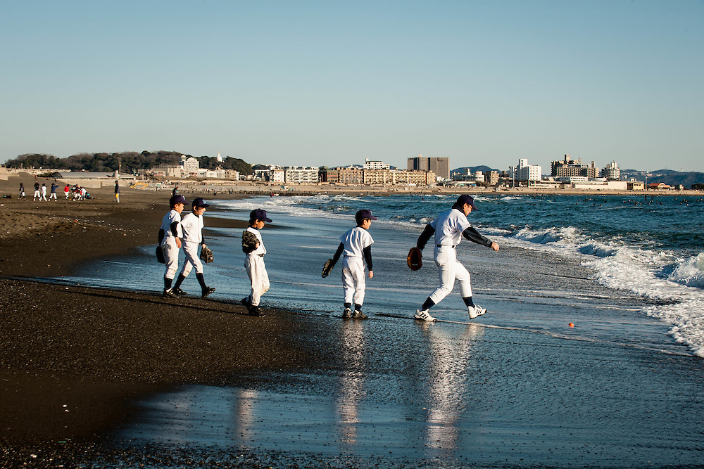 A coach and players try to save a ball from the ocean during baseball practice at Kugenuma Beach in Fujisawa, Japan.