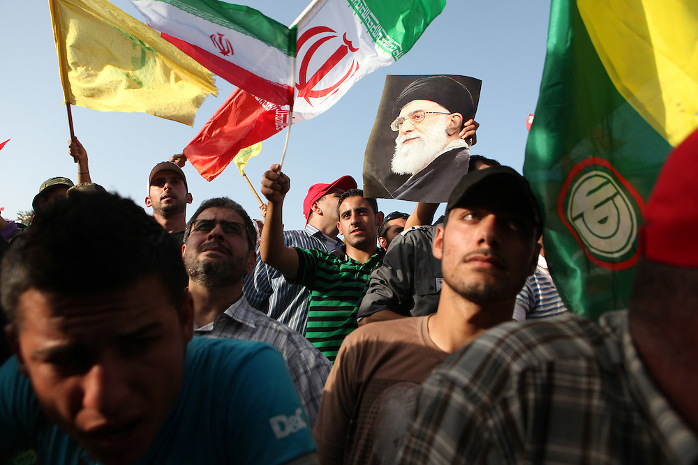 On the second and final day of his visit to Lebanon, Iranian President Mahmoud Ahmadinejad traveled to the southern town of Bint Jbeil. There a Hizballah-organized rally was held to welcome Ahmadinejad to the south Lebanon, an area where Hizballah is widely supported. Tens of thousands gathered for hours holding flags of Iran, Hizballah, Lebanon and other political parties, cheering the Iranian president as he arrived by helicopter from Beirut. ///A man holds a picture of Iran's Supreme Leader Ayatollah Khamenei waiting for Iranian President Mahmoud Ahmadinejad to address the crowd.