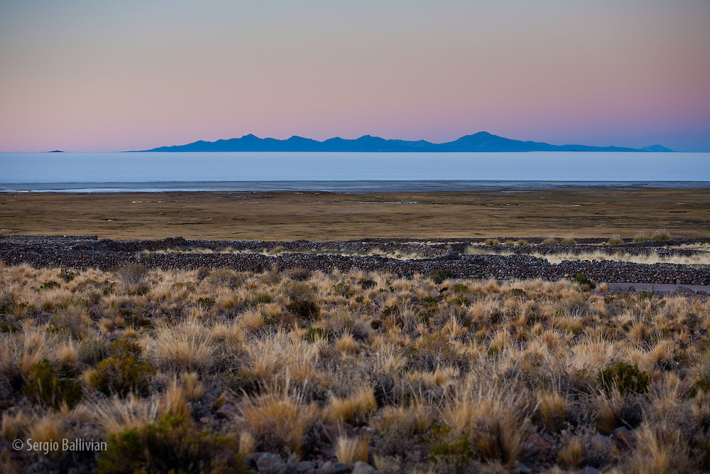 Sunrise colors on the  Salar de Uyuni salt flat in south-western Bolivia as seen from the dry land on the northern edge near the village of Jirira.