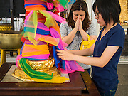 12 MARCH 2015 - BANGKOK, THAILAND:  Women pray and make merit at the City Pillar Shrine in Bangkok. Bangkok's city pillar shrine (also known as San Lak Muang) is one of the most important city pillar shrines in Thailand. The shrine is in the heart of Bangkok, opposite the grand palace in the southeast corner of the Sanam Luang and close to the Ministry of Defence. The shrine was built after the establishment of the Rattanakosin Kingdom (Bangkok) to replace the old capital of the Thonburi Kingdom during the reign of King Rama I in 1782. It was intended to be the spiritual center for Thai citizens.     PHOTO BY JACK KURTZ