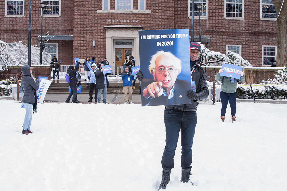 """Brooklyn, NY - 2 March 2019. An African-American man holds a large sign reading """"I'm coming for you Trump in 2020"""" at Bernie Sanders' first rally for the 2020 presidential primary at Brooklyn College."""