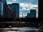 The Chicago River on a Friday afternoon at sunset, with the light reflected off the water onto the underside of the bridges