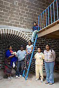 San Miguel de Allende, Guanajuato, Mexico, 8/29/08: Antonio Nolasco and his family, l-r: wife Consuela Ramirez Nolasco, with grandson David, Antonio, daughters Maria del Carmen, Gloria on ladder, daughter-in-law Brenda Yanez, daughter Veronica Ramirez Nolasco, int the home which was built by Casita Linda. It is a Mexican non-profit organization, started and run by North Americans, which builds adobe homes for families in extreme poverty (photo: Ann Summa).