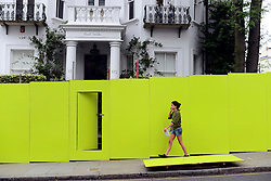 © Licensed to London News Pictures. 24/08/2012. London, UK. A woman walks past a Paul Smith building. Shops and premises are boarded up today 24th August 2012 ahead of the Notting Hill Carnival which takes place this weekend.  Photo credit : Stephen Simpson/LNP