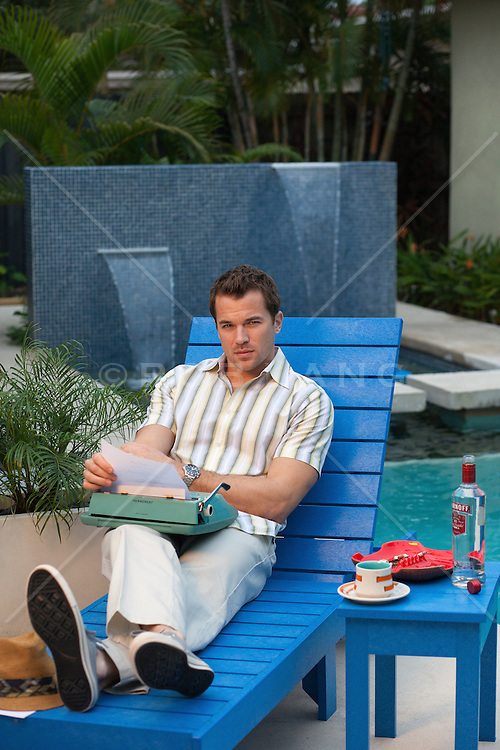 50's syled man working on a typewriter while reclining by a swimming pools on a lounge chair