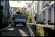 Truck stacked with sycamore rolls down street as men decorate town with branches for May Day; Padstow, Cornwall, England.