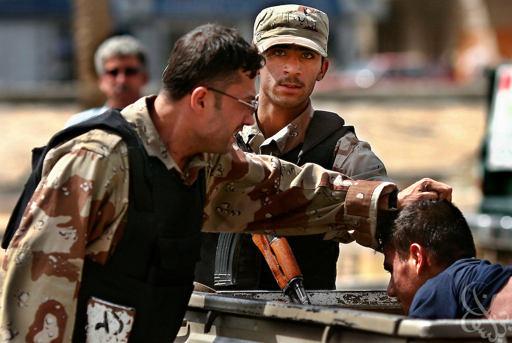 Iraqi Army soldiers detain a suspect at gunpoint near the scene of a bomb attack at a market in central Baghdad, Iraq June 17, 2006.