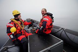 LABRADOR SEA 16JUN11 - Boat crew Sune Scheller of Denmark (L) and third mate Kevin Bell of the USA during boat training from aboard the Greenpeace ship Esperanza in the Davis Stait off the coast of Greenland.....Photo by Jiri Rezac / Greenpeace