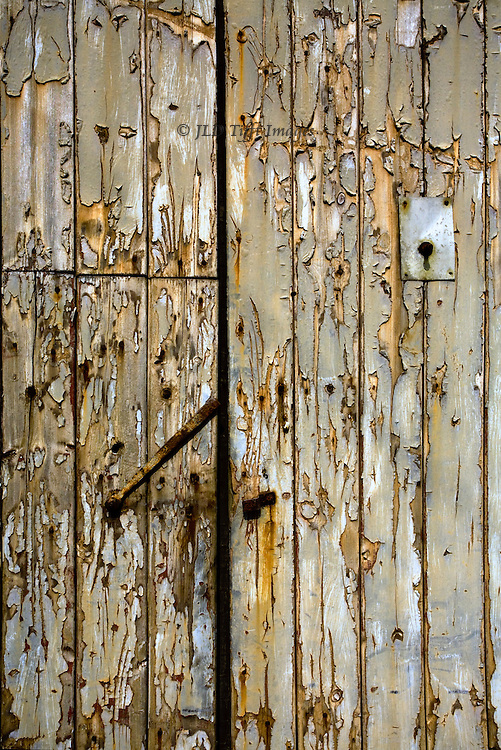Kettlewell, Upper Wharfedale : wooden barn door with rusted latch and peeling paint making a texture