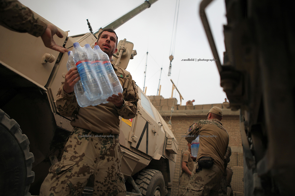 Soldiers stand in a line to deliver water bottles into their District Headquarters in Nawabad. In late October 2011 Kunduz based 3.Task Force started a several days operation in and around Nawabad (District Chahar Darah), west of Kunduz, northern Afghanistan. During the Operation Orpheus about 100 german infantery soldiers rolled out for patrols through the town and surrounding areas, which were expected as a retreat zone of insurgents.