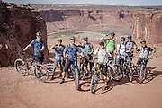 SHOT 10/14/16 2:04:28 PM - Group picture before riding the White Rim Trail. The White Rim is a mountain biking trip in Canyonlands National Park just outside of Moab, Utah. The White Rim Road is a 71.2-mile-long unpaved four-wheel drive road that traverses the top of the White Rim Sandstone formation below the Island in the Sky mesa of Canyonlands National Park in southern Utah in the United States. The road was constructed in the 1950s by the Atomic Energy Commission to provide access for individual prospectors intent on mining uranium deposits for use in nuclear weapons production during the Cold War. Four-wheel drive vehicles and mountain bikes are the most common modes of transport though horseback riding and hiking are also permitted.<br /> (Photo by Marc Piscotty / &copy; 2016)