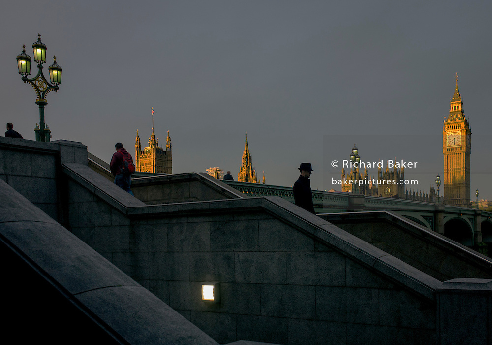 Dawn light and silhouetted people with the Palaces of Westminster, Britain's parliament building on the far side of Westminster Bridge on the River Thames.