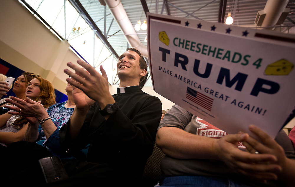 """Jonathan Heinricy, left, applauds during Republican Presidential candidate Donald Trump's """"Make America Great Again Rally"""" at the Grand River Center in Dubuque, Iowa, Tuesday, August 25, 2015. REUTERS/Ben Brewer"""