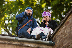 Housing activists take refuge from bailiffs trying to evict them on a roof on the Sweets Way housing estate on 23rd September 2015 in London, United Kingdom. (2nd sentence - Why). A group of housing activists calling for better social housing provision in London had occupied some of the properties on the 142-home estate in Whetstone, in some cases refurbishing properties intentionally destroyed by the legal owners following eviction of the original residents, in order to try to prevent the eviction of the last resident on the estate and the planned demolition and redevelopment of the entire estate by Barnet Council and Annington Property Ltd.