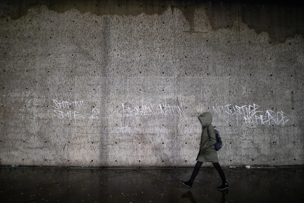 "© Licensed to London News Pictures . 21/12/2018 . Manchester , UK . A woman walks past architect Tadao Ando's concrete wall in Piccadilly Gardens , which has had the words "" Stop the Spice "", "" Broken Nation "" and "" No Justice No Peace "" painted across it . Mad Friday in Manchester City Centre - named for historically being one of the busiest nights of the year for the emergency services in the UK  . Photo credit : Joel Goodman/LNP"