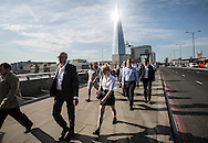Date: 01/07/15 <br /> PH:  Nick Edwards<br /> Pictured: Commuters make their way to work across London Bridge, with the sun reflecting from the Shard, London's tallest building<br /> Caption: Commuters make their way to work across London Bridge in the sun this morning on what is set to be the hottest day in 9 years. Temperatures are set to reach 34 degrees. Heath alerts have been issued and a level 3 heatwave. The hot weather is due to last all week.