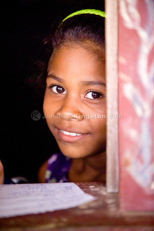Portrait of a Miskito girl looking up from her school work in Krin Krin, Nicaragua.
