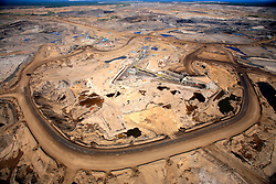 CANADA ALBERTA FORT MCMURRAY 20JUL09 - Aerial view of Syncrude Aurora tarsands mine in the Boreal forest north of Fort McMurray, northern Alberta, Canada...The tar sand deposits lie under 141,000 square kilometres of sparsely populated boreal forest and muskeg and contain about 1.7 trillion barrels of bitumen in-place, comparable in magnitude to the world's total proven reserves of conventional petroleum. Current projections state that production will  grow from 1.2 million barrels per day (190,000 m³/d) in 2008 to 3.3 million barrels per day (520,000 m³/d) in 2020 which would place Canada among the four or five largest oil-producing countries in the world...The industry has brought wealth and an economic boom to the region but also created an environmental disaster downstream from the Athabasca river, polluting the lakes where water and fish are contaminated. The native Indian tribes of the Mikisew, Cree, Dene and other smaller First Nations are seeing their natural habitat destroyed and are largely powerless to stop or slow down the rapid expansion of the oil sands development, Canada's number one economic driver...jre/Photo by Jiri Rezac / GREENPEACE..© Jiri Rezac 2009