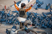 Girl playing with pigeons at Pushkar lake ghats (India)