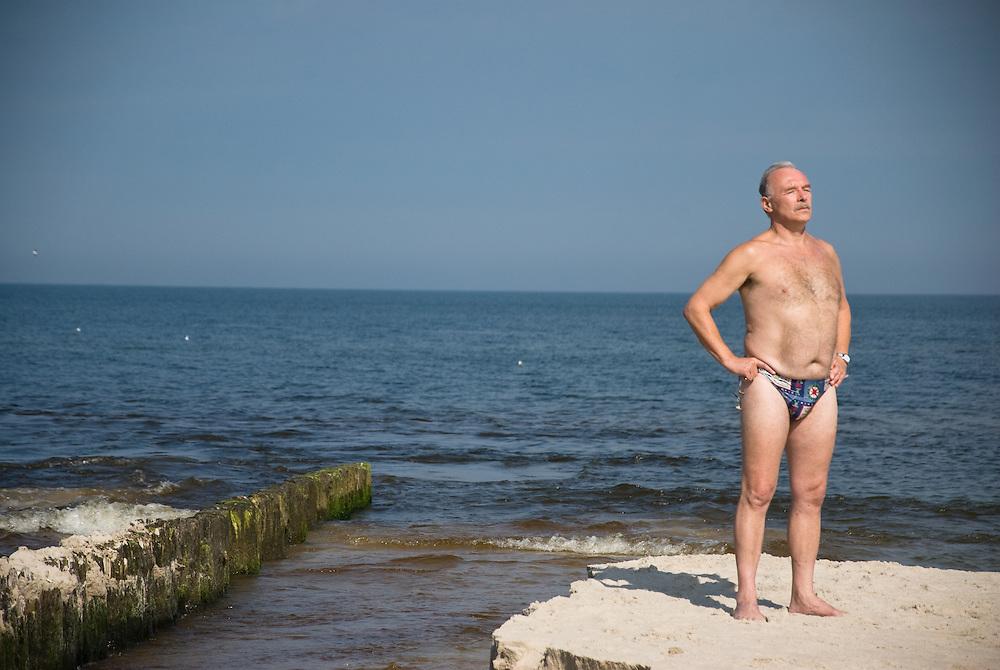 A man sunbathing by the Baltic sea at Karwia, Pomorze, Poland, Sepember 2011.