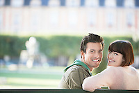 Young couple sitting on bench head and shoulders in park
