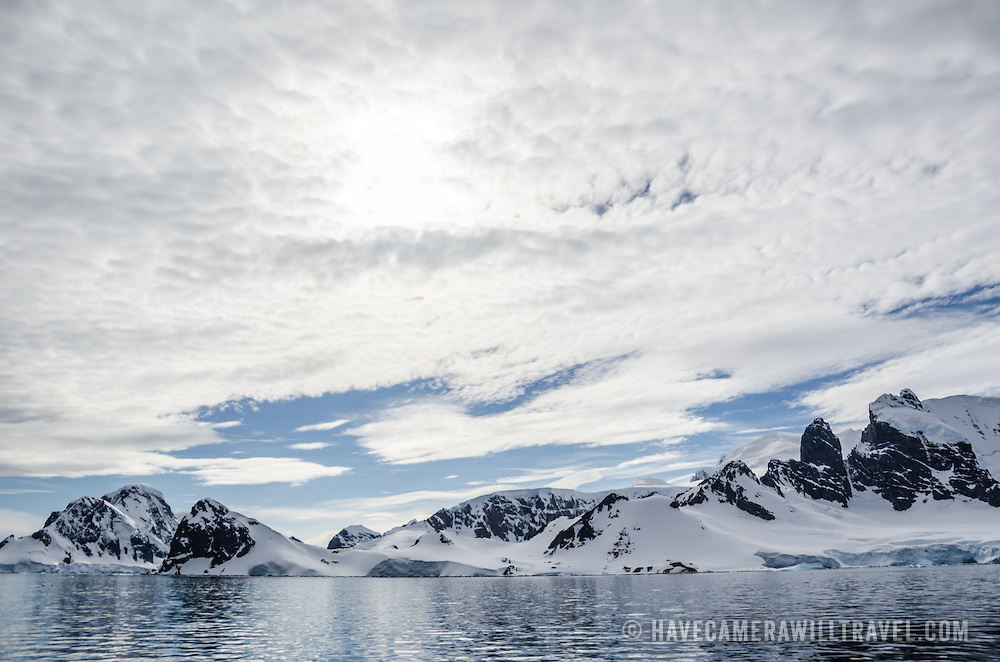 A light layer of high clouds partially obscures the sun above Cuverville Island on the western side of the Antarctic Peninsula.