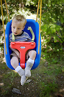 JEROME A. POLLOS/Press..Gavin Scheel, 2, sits in his swing while his father mows the lawn Friday.