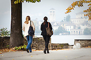 Two women walking down the road near Orta San Giulio with Isola San Giulio and its monastery in the distance, Piedmont, Italy