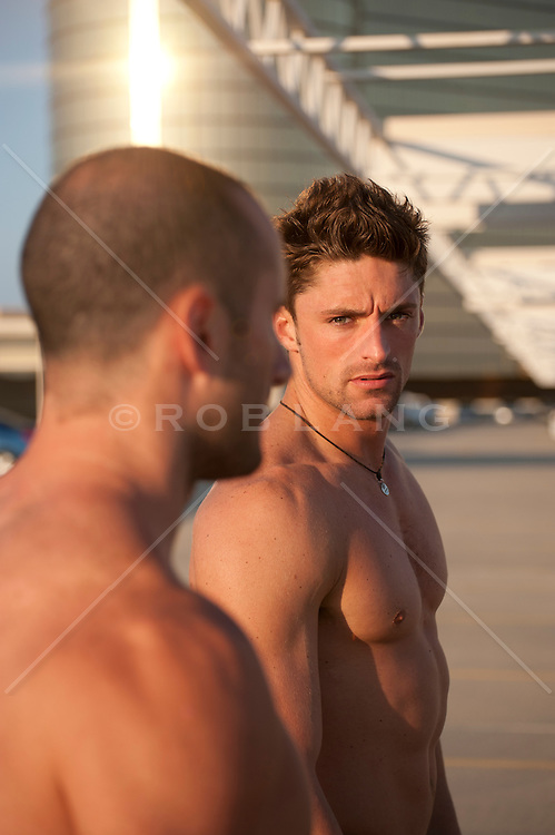 Two shirtless men on a rooftop building