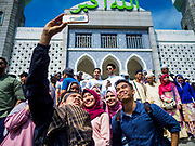 "15 JUNE 2018 - SEOUL, SOUTH KOREA: Muslims from Indonesia pose for ""selfies"" at Seoul Central Mosque on Eid al Fitr, the Muslim Holy Day that marks the end of the Holy Month of Ramadan. There are fewer than 100,000 Korean Muslims, but there is a large community of Muslim immigrants in South Korea, most in Seoul. Thousands of people attend Eid services at Seoul Central Mosque, the largest mosque in South Korea.   PHOTO BY JACK KURTZ"