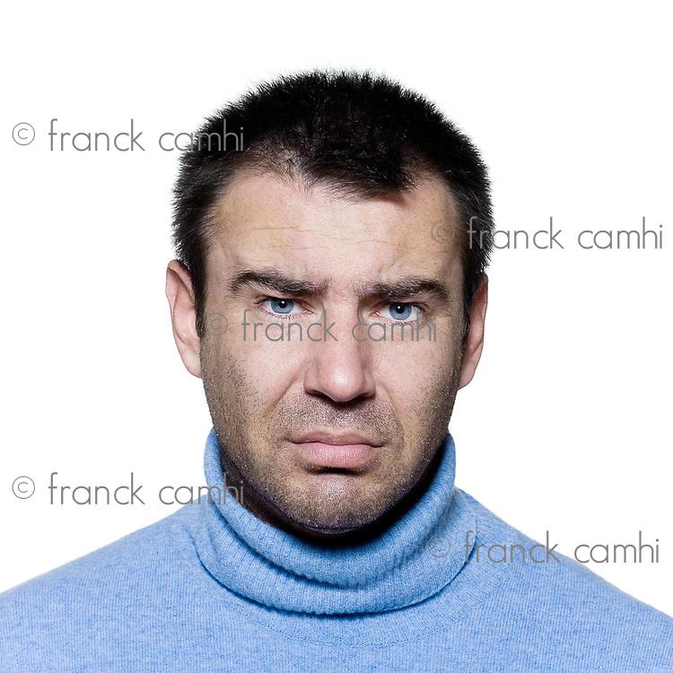 studio portrait on isolated background of a stubble man sad pucker