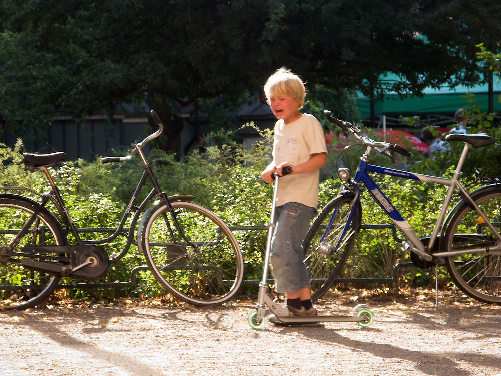 A crying boy pushes his scooter in Stockholm.