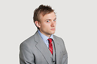 Portrait of angry young businessman over light gray background