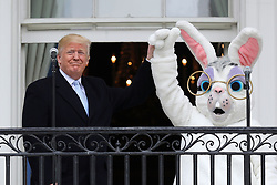WASHINGTON, DC - APRIL 02: AFP OUT U.S. President Donald Trump (L) lifts the hand of a person in an Easter Bunny costume on the Truman Balcony during the 140th annual Easter Egg Roll on the South Lawn of the White House April 2, 2018 in Washington, DC. The White House said they are expecting 30,000 children and adults to participate in the annual tradition of rolling colored eggs down the White House lawn that was started by President Rutherford B. Hayes in 1878. (Photo by Chip Somodevilla/Getty Images)
