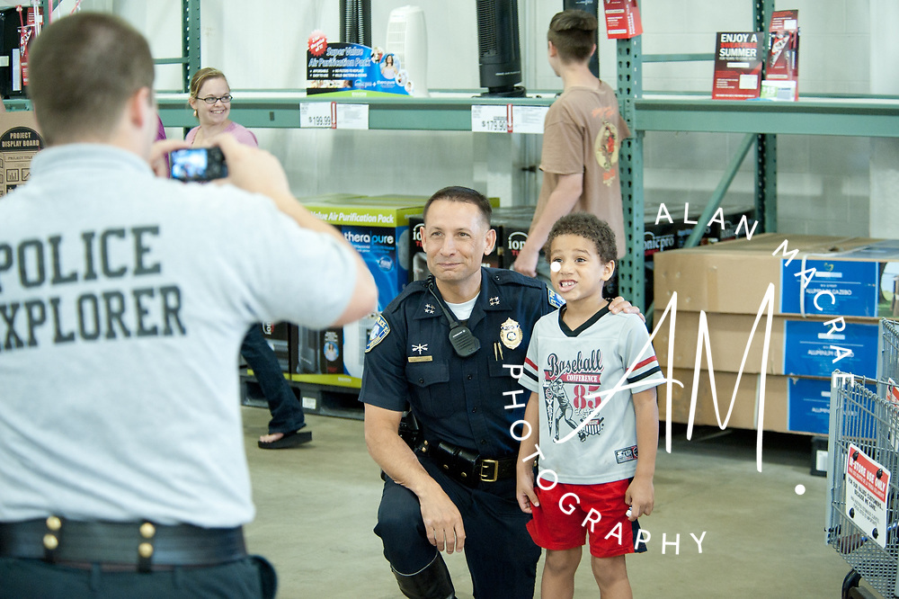 Five-year-old Jordan Flores of Laconia poses with Tilton Police Chief Bob Cormier during Saturday's Health and Safety Fair at BJ's Wholesale Club in Tilton.  (Alan MacRae/for the Citizen)