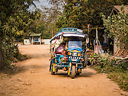 11 MARCH 2016 - LUANG PRABANG, LAOS:   A tuk-tuk (three wheeled taxi) drives through the community of Chomphet, across the Mekong River from Luang Prabang. Laos is one of the poorest countries in Southeast Asia. Tourism and hydroelectric dams along the rivers that run through the country are driving the legal economy.     PHOTO BY JACK KURTZ