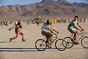 Roller blader pulled by bicycles at Burning Man. Burning Man is a performance art festival known for art, drugs and sex. It takes place annually in the Black Rock Desert near Gerlach, Nevada, USA.