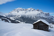 A snow covered wooden barn at the Alta Badia ski resort with Lavarella and Contourines mountains in the background.  Corvara, The Dolomites, South Tyrol, Italy