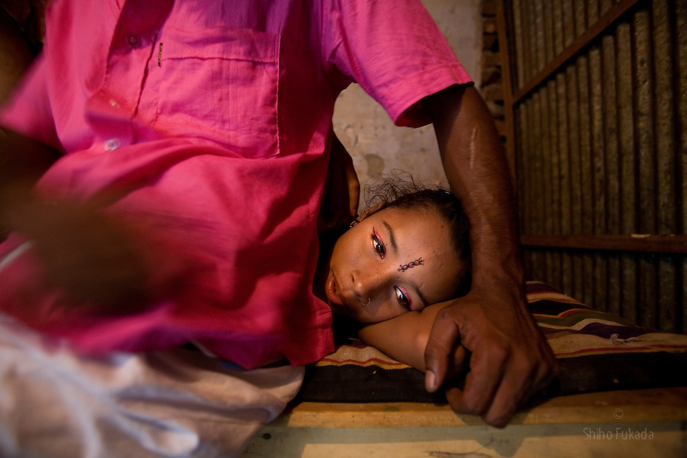 Sex worker Nodi,14, lies down by  a customer at brothel, June 9, 2007 in Tangail, Bangladesh. Nodi run away from home after falling in love with a Hindu boy and ended up in the brothel with her sister.<br /> The majority of the 20,000 to 30,000 female sex workers in Bangladesh are victims of trafficking. <br /> Once they enter the brothel, usually before the age of 12, they are generally in for life because of social stigma and poverty.