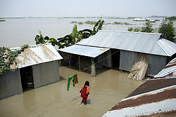August 15, 2017 - Dhaka, Bangladesh - A woman walks around her flooded yard around the house. (Credit Image: © K M Asad via ZUMA Wire)