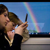 Commuters traveling on a New Jersey Transit North Jersey Coast Line commuter train carry on with there business as a rainbow appears after a passing storm in the early evening.