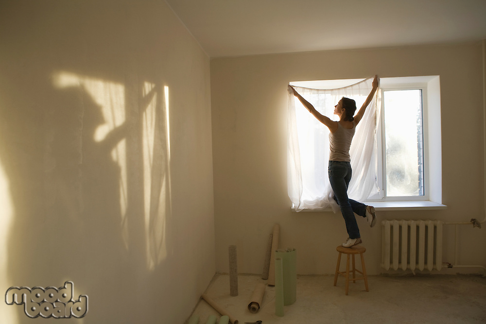 Woman fitting curtains in new apartment