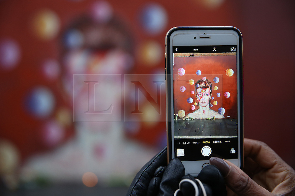 © Licensed to London News Pictures. 11/01/2016. London, UK. A woman takes a phone photo of a mural of David Bowie in Brixton. The Death of David Bowie, who was born in Brixton, has been announced today.  Photo credit: Peter Macdiarmid/LNP