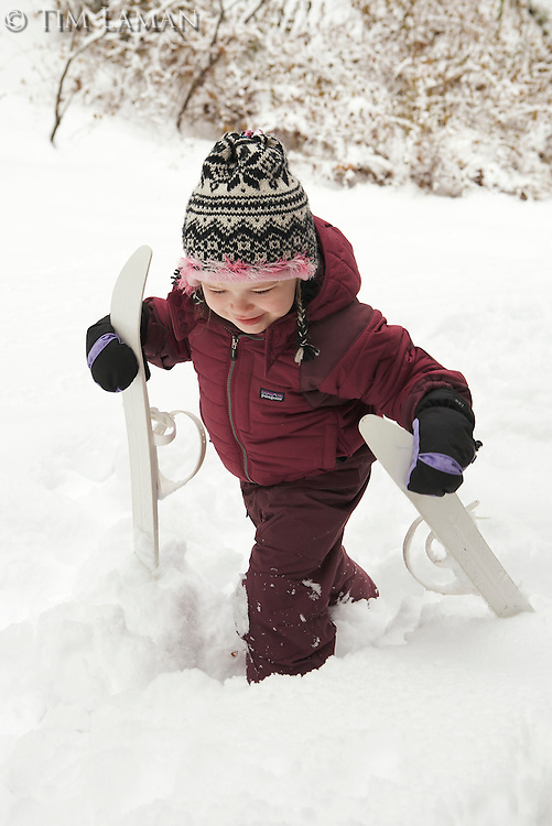 A 4 year old girl takes her skis out to the fresh snow in the back yard.